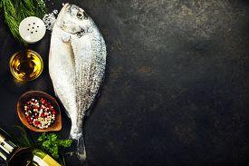 stock photo of sea fish  - Delicious fresh fish on dark vintage background - JPG
