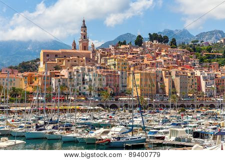 Old colorful houses overlooking small marina with yachts and boats in Menton - town on French Riviera.