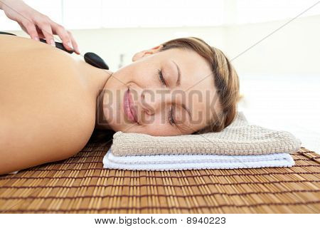 Portrait Of A Beautiful Woman Lying On A Massage Table With Hot Stones