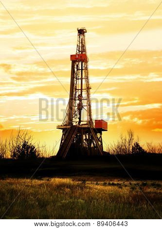 Natural gas production, land drilling rig at sunset.