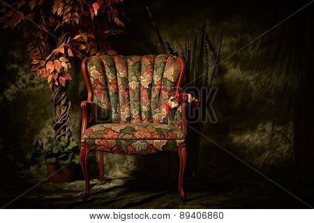 Antique Empty Chair With Colorful Pattern And Plant.