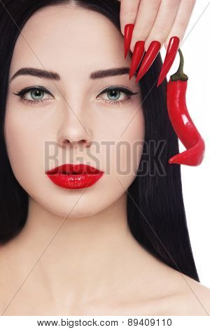 Portrait of young beautiful brunette with red lipstick, long stiletto nails and hot chili pepper in her hand over white background