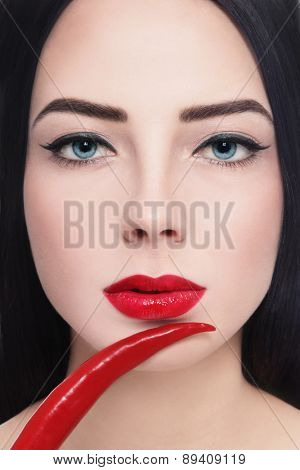 Close-up portrait of young beautiful brunette with red lipstick and hot chili pepper