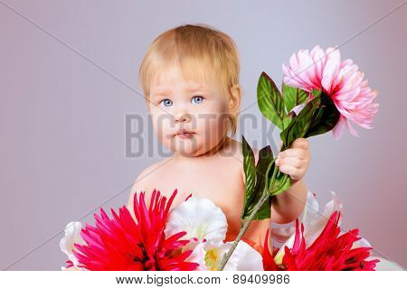 Sweet little baby girl sitting among flowers. Beauty, childhood. Healthcare.