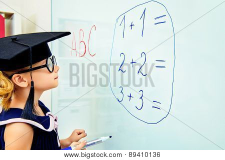 Cute little student girl in academic hat during the lesson at school. Educational concept.