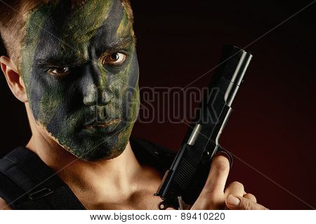 Close-up portrait of a brave soldier in war paint holding a gun. Black background. Military, war. Special forces.
