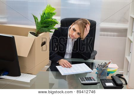 Businesswoman At Desk With Belongings In Box
