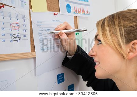 Businesswoman Writing On Weekly Time Sheet