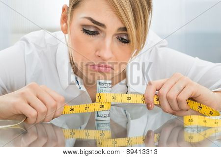 Unhappy Businesswoman With Measuring Tape And Banknote