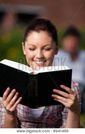 Smiling Female Student Reading A Book Sitting On Grass