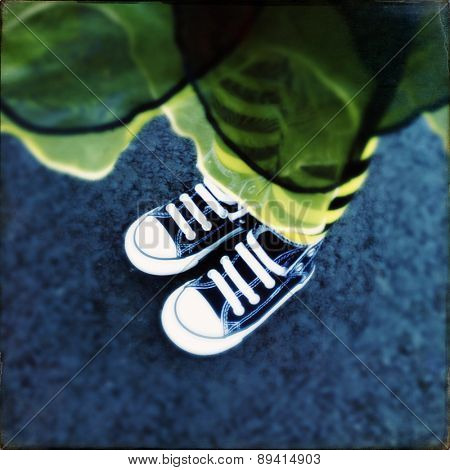 Instagram filtered image of a toddler girls feet with yellow and black leggings (soft focus)