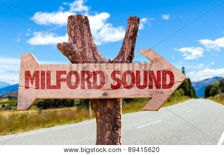 Milford Sound wooden sign with road background