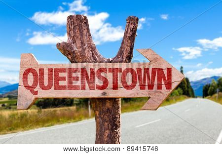 Queenstown wooden sign with road background
