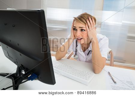 Worried Doctor Looking At Computer