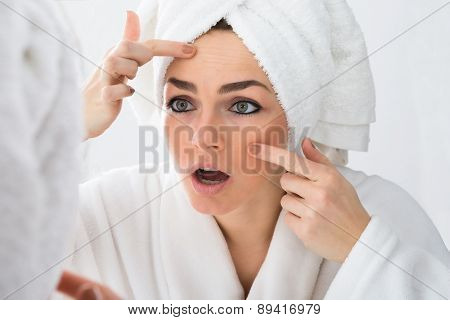 Worried Woman Looking At Pimple On Face