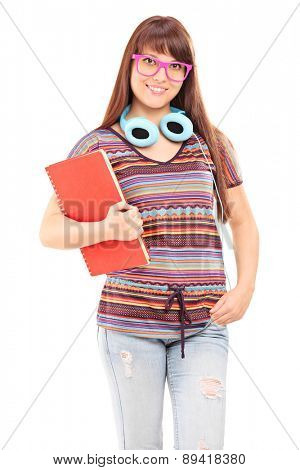 Vertical shot of a young female student holding a notebook and wearing blue headphones around her neck isolated on white background