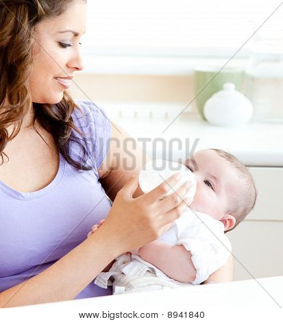 Radiant Mother Feeding Her Adorable Son In The Kitchen