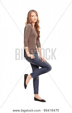 Full length profile shot of a casual young woman leaning against a wall and posing isolated on white background