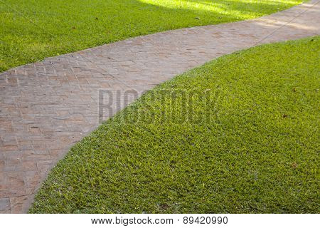 Curved Red Brick Walkway With Green Grass