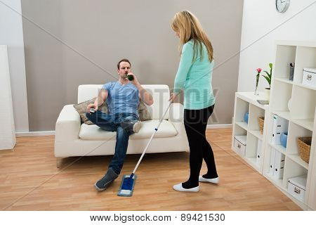 Woman Wiping Floor While Man Drinking Alcohol