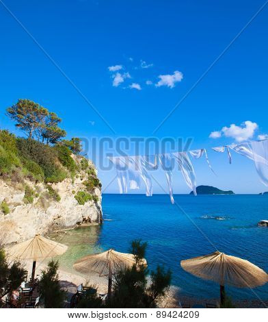Row of Straw umbrellas and lounges at beach Zakynthos, Greece.