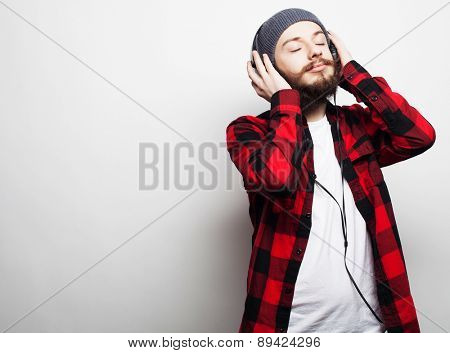 life style, education and people concept:  young bearded man listening to music while standing against grey background. Hipster style.