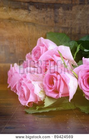 Vintage Pink Roses On Dark Wood Background.