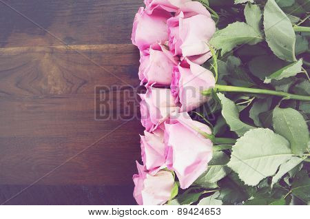 Vintage Pink Roses On Dark Wood Background.