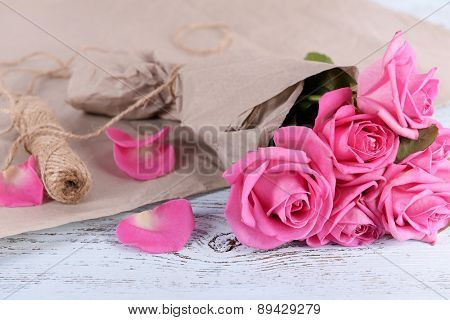 Beautiful pink roses on wooden table with parchment, closeup