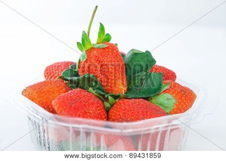 Closed Up Strawberry In Plastic Box On White
