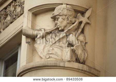 Man with a lamp and an axe trumpeting a bugle. Art Nouveau building decoration at Bubenecska Street in Prague, Czech Republic.