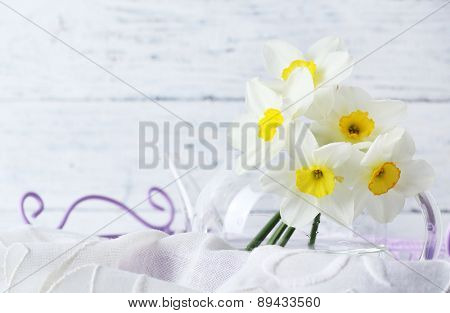 Fresh narcissus flowers in tray on wooden background