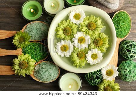 Beautiful composition with sea salt in wooden spoons and flowers on table close up
