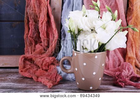 Beautiful flowers in cup on fabric background