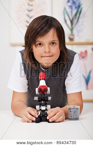 School boy in science class with microscope and young plant - study biology