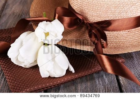 Hat with flowers on wooden background, closeup