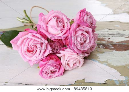 Beautiful fresh roses on wooden table, closeup