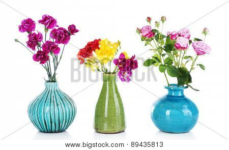 Different beautiful flowers in vases isolated on white