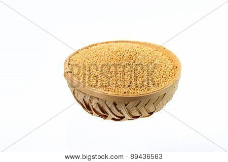 yellow mustard seeds in wooden basket isolated on white background