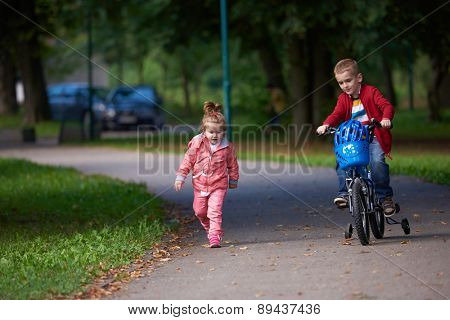happy kids in park, boy and girl in nature with bicycle have fun