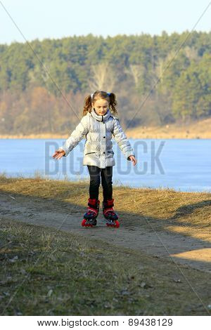 young girl goes in roller skates on the ground