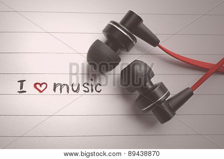 Earphones on notebook with text I Love Music, closeup