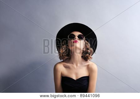 Portrait of beautiful model in black dress, hat and sunglasses on gray background