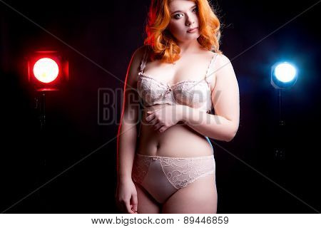 Overweight Girl In Lijerie On Black Background With Two Lights Behind