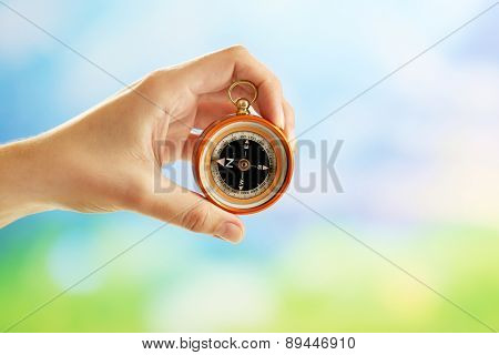 Female hand with compass on bright blurred background