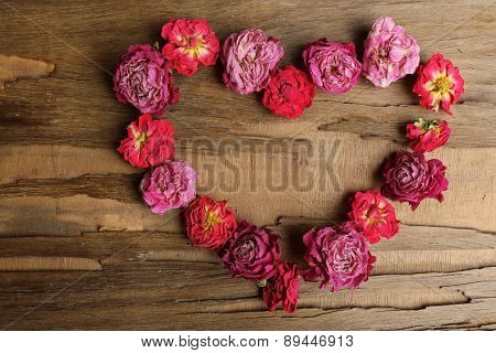 Heart of beautiful dry flowers on wooden background