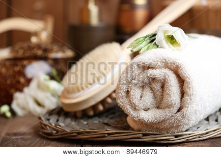 Beautiful spa composition with towels and flowers on table close up