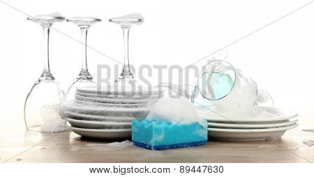 Dishes in foam with gloves and wisp on table isolated on white