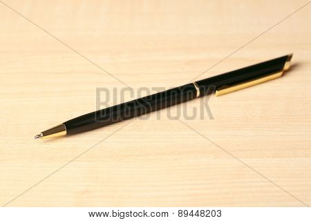 Ballpoint pen on wooden table background