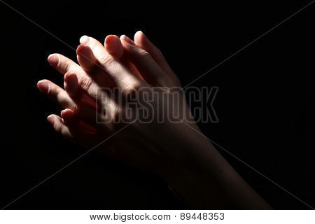 Woman praying in darkness